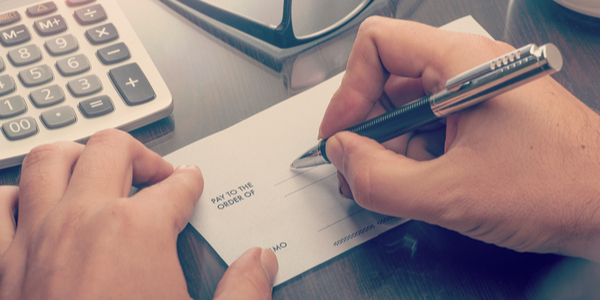 person writing a check with a pen